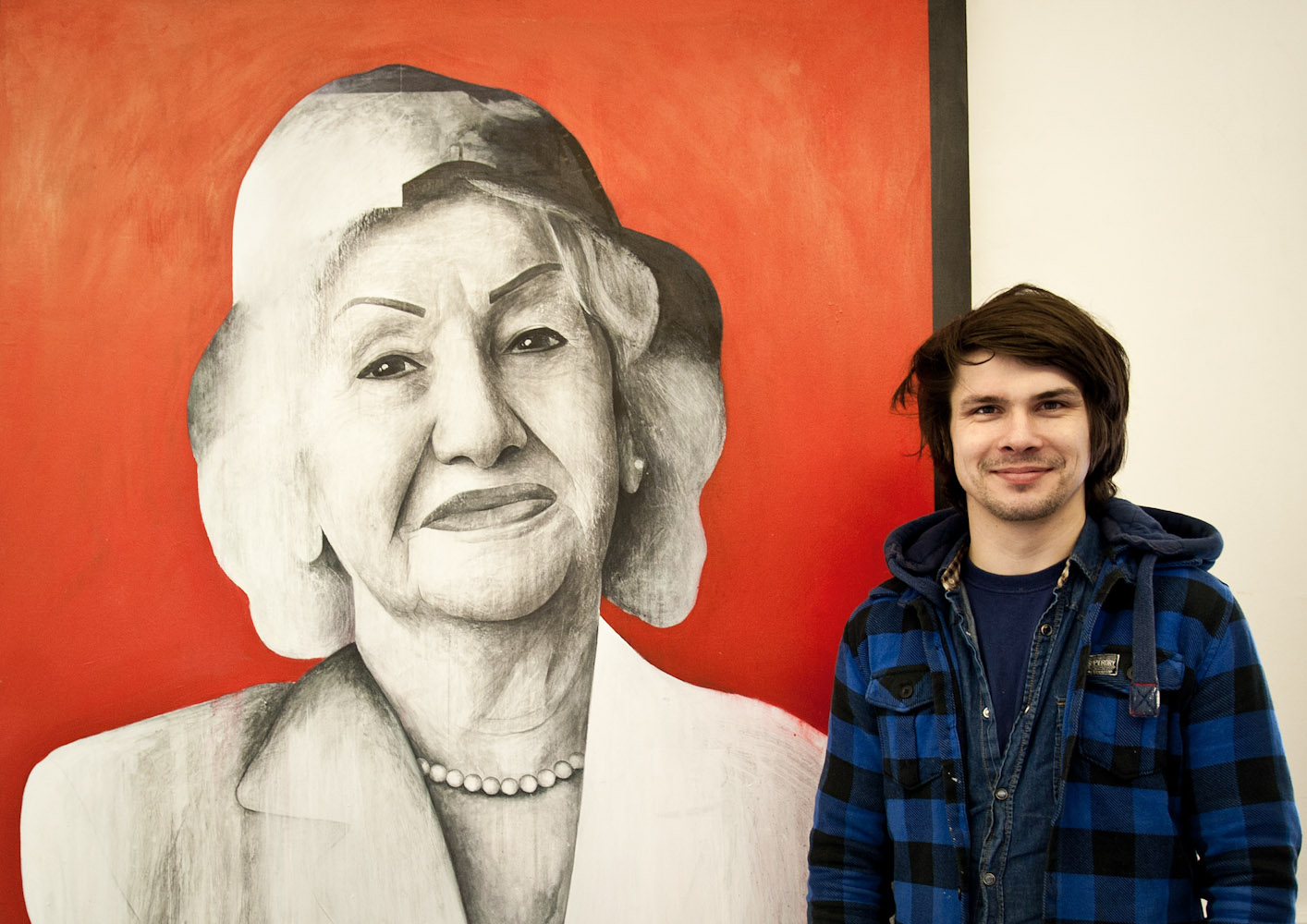 Ben Slow standing next to his painting of Fatemah Feshangchi